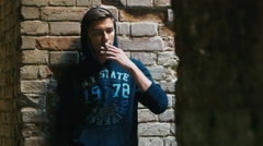 Young man smokes in an abandoned house. Concept: despair, unemployment - stock footage