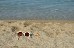 Sun glasses with sea star on a beach Stock Photos