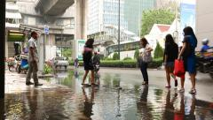 Woman slowly step on small stones, cross over puddle on roadway Stock Footage