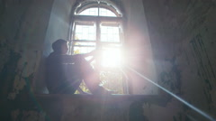 Man with a gun at the window in the sun. Concept: Hope, Crime, a ray of hope Stock Footage