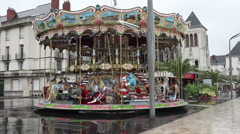 Merry-Go-Round (carousel) on a rainy day, reflection on the pavement, France Stock Footage