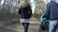 Family ride with baby carriage park from back. Family idyll. 4K Stock Footage
