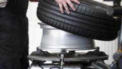 Car mechanic assembling tire on wheel - stock footage