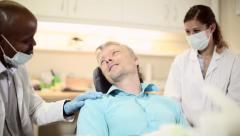 Dentist talks to patient before examination while nurse watches Stock Footage