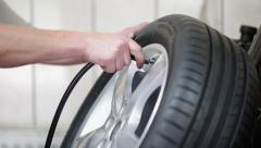 Car mechanic pumping alloy wheel Stock Footage