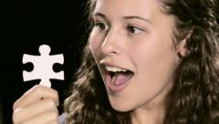 Puzzled young beauty inspects a white jigsaw puzzle piece Stock Footage