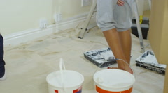 4K Happy attractive mixed ethnicity couple painting a wall in new home Stock Footage
