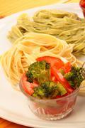 Two italian tagliatelles and tomato with broccoli condiment Stock Photos