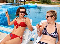 Two beautiful girls in bikini drinking champagne Stock Photos