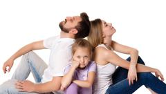 The tired family sitting on white background - stock photo