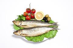 Smoked sprat-appetizing snack with tomato and lemon - stock photo