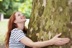Pretty Blond Teen Girl Admiring a Tall Tree Stock Photos