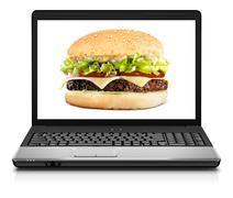 Laptop computer close-up with cheeseburger - stock photo
