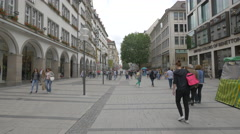Girl with backpack and other people walking on Neuhauser Strasse, Munich Stock Footage