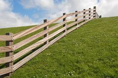 Wooden fence on a dyke. - stock photo