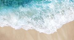 Soft wave of the sea on the sandy beach Stock Photos