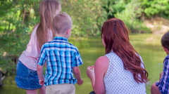Family feeding the animals in pond - stock footage