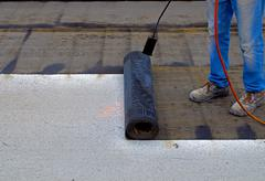 Worker preparing part of bitumen roofing felt roll for melting by gas heater - stock photo