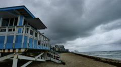 Medium angle view time-lapse of lifeguard house under fast stormy clouds Stock Footage