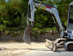 Mini excavator dig a trench with a bucket micro very tight - stock photo