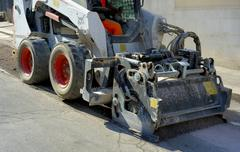 Milling of asphalt for road reconstruction accessory for skid steer - stock photo