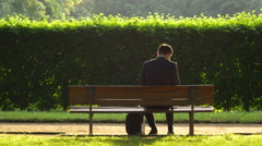 Man sitting down on a bench in the park, Munich Stock Footage