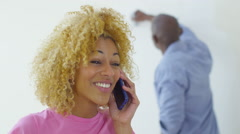 4K Happy couple in new home, woman makes a phone call while man paints - stock footage