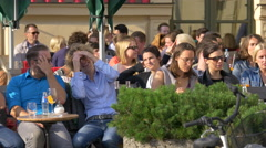 Friends talking and relaxing at an outdoor restaurant in Munich Stock Footage