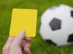 Stock Photo of referee hand with yellow card