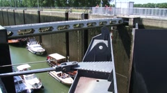 Lock gate opens, low lying recreational vessels prepare to sail out Stock Footage