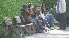 Girls sitting down and talking in Hofgarten, Munich Stock Footage