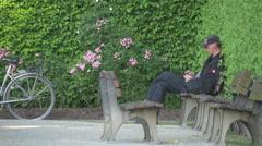 Man relaxing on a bench in Hofgarten, Munich Stock Footage