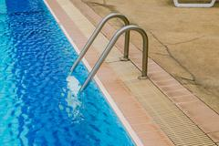 Swimming pool with stair at hotel. - stock photo