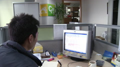 Chinese man at computer in modern office Stock Footage