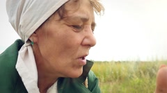 Aged woman smoking a cigarette in a scarf on the nature and coughs Stock Footage