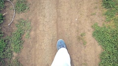 Slowmotion of Walking legs in shoes on the road in nature outdoor.fly butterfly Stock Footage