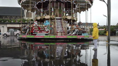 Two boys in yellow raincoats watching merry-Go-Round (carousel) on a rainy da Stock Footage