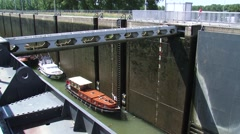 Lock gate opened, low lying recreational vessels move out Stock Footage