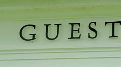 The letter GUESTHOUSE on the wall outside Stock Footage