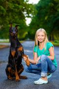 blonde girl holding dog or doberman paw in summer park - stock photo