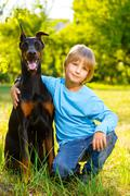 boy hugs his beloved dog or doberman in summer park - stock photo