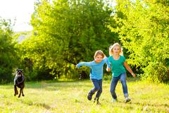 boy and a girl running away from dog or doberman in summer park - stock photo