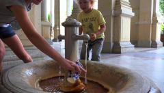 Children pour water into the cup at the Mill Colonnade Healing Spring. - stock footage