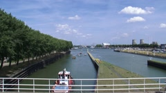Traffic + cyclists across Lock complex + low lying vessels sail out Stock Footage