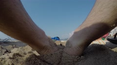 Male sitting on a hot sandy beach at the ocean Stock Footage