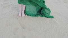 Beauty Girl in green dress running on sand dune while wind blowing her clothes Stock Footage