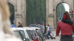 Riding bikes and driving towards the Siegestor, Munich Stock Footage