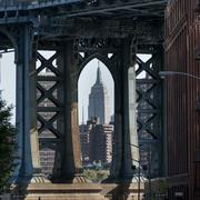 View of the Empire State Building through Manhattan Bridge - stock photo
