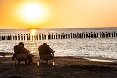 People on the sunbeds at sunset Stock Photos