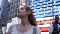 close-up of beautiful female traveler looking up around Times Square with map - stock footage